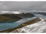 Výhľad zo sedla Gampa-La (4 800m) na posvätné tyrkysové jazero Yamdrok-Tso. Jeho dlĺžka je 72 km.